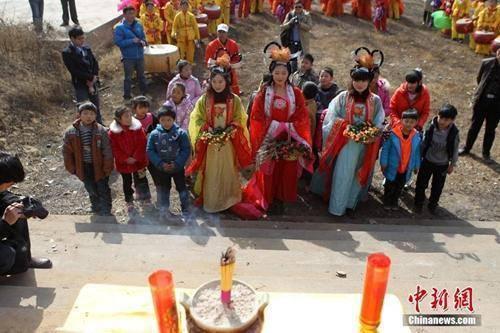 """资料图:民众在""""春姑娘""""的带领下祭拜灶神。 中新社发 王中举 摄"""