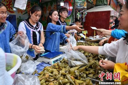 资料图:6月5日,商贩身穿少数民族服饰售卖特色粽子。中新社记者  任东 摄
