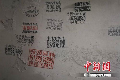 图为北京一小区楼道内的空调维修小广告。 谢艺观 摄