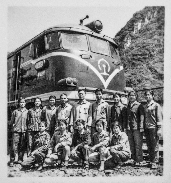 广西第一代女火车司机在内燃机车前合影留念。(资料图片,受访者供图)