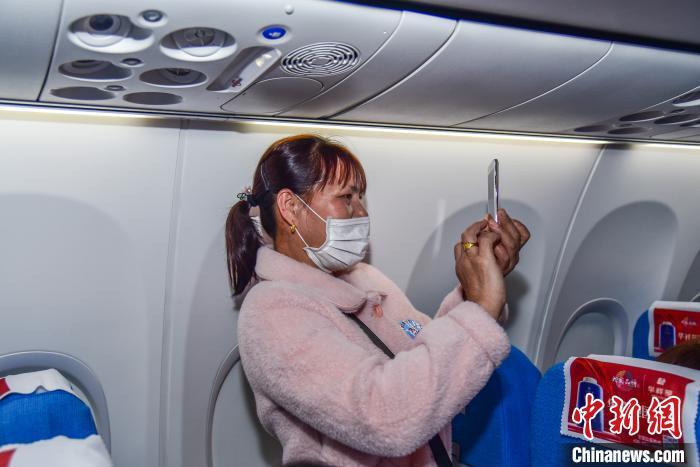 务工人员使用手机拍摄飞机内的画面与亲友分享。 王以照 摄