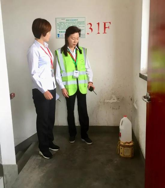 31楼,就看到原本放垃圾桶的位置叠放着一个空矿泉水桶和水果竹篮。