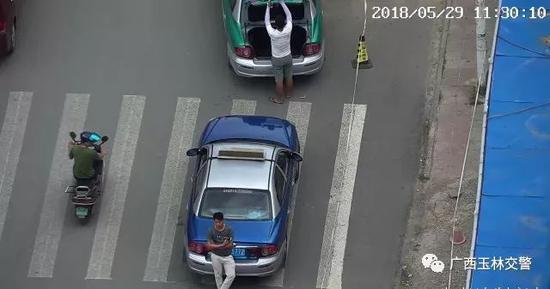 男子斑马线上违法停车,用身体遮挡号牌。