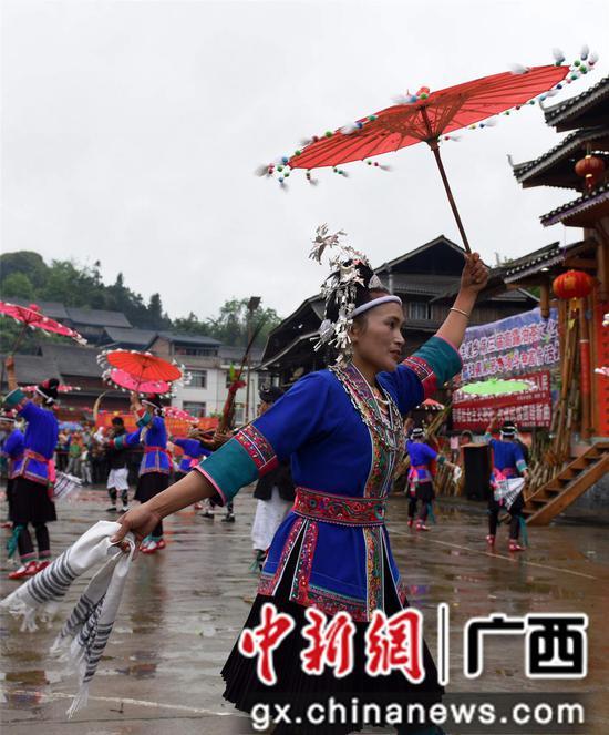 4月14日,在三江侗族自治县洋溪乡高露村中寨屯,一名妇女在表演民族舞蹈。龚普康 摄