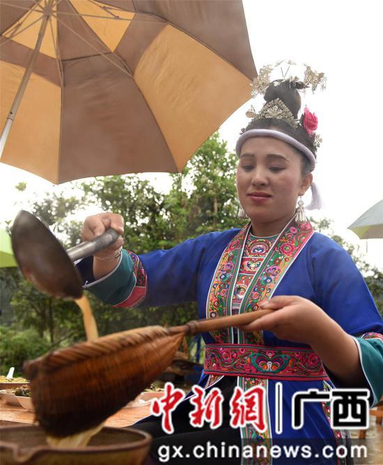 4月14日,在三江侗族自治县洋溪乡高露村中寨屯,一名侗族妇女在打油茶。龚普康 摄