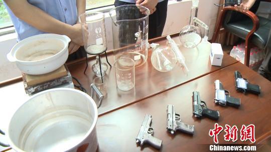 图为缴获的仿制式手枪及制毒工具设备。 钟欣 摄