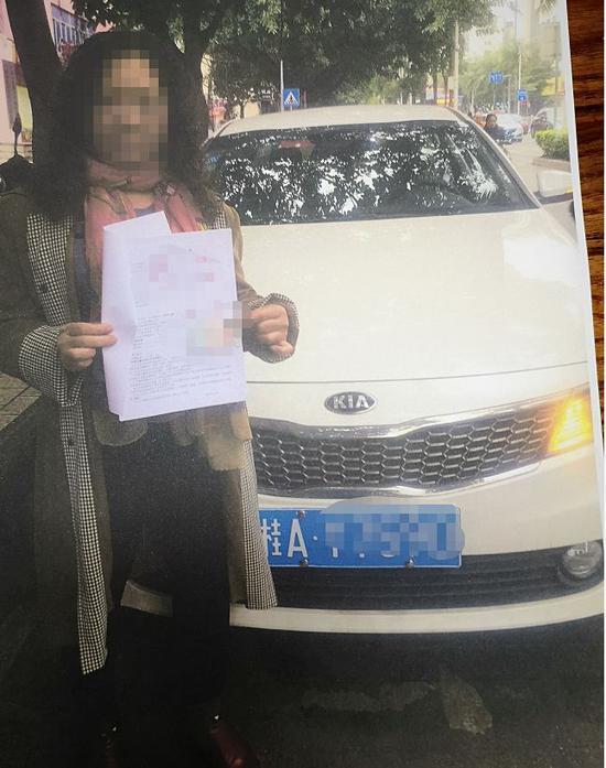 谢女士手持质押协议和身份证与车子的照片