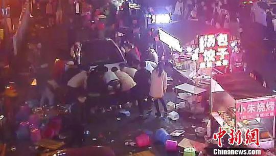 图为监控显示民众抬车救人。 梁俭 摄