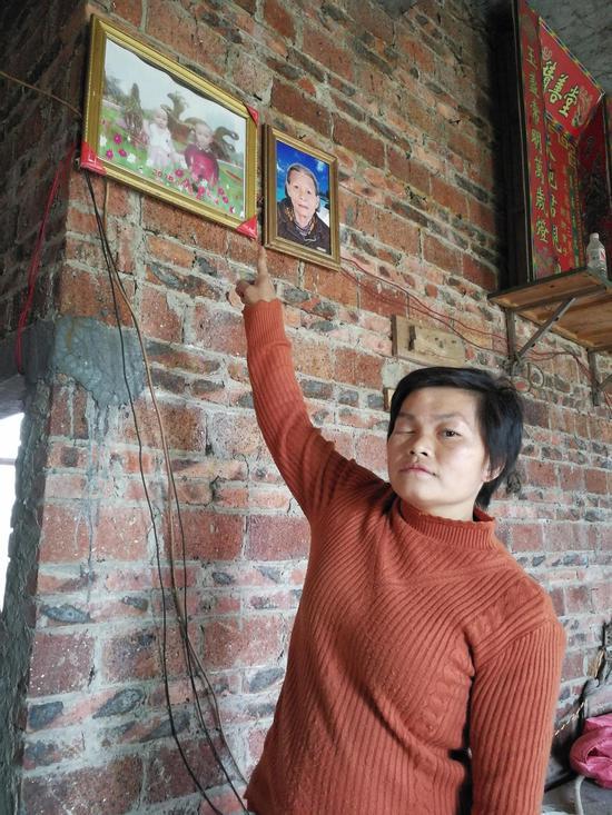 2015年9月30日,覃美欢的两个女儿和婆婆被杀害,其遗像挂在墙上。覃美欢和儿子则受重伤。澎湃新闻记者 朱远祥 摄