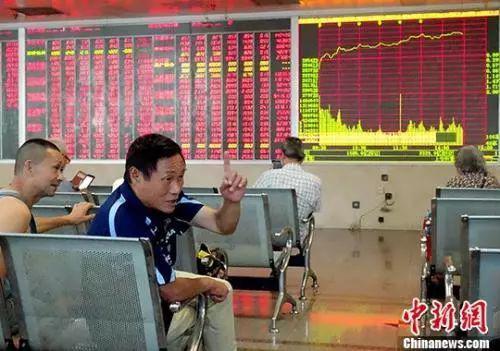 资料图:成都某证券交易大厅内,股民正在交流自己的股票涨势情况。中新社记者 刘忠俊 摄