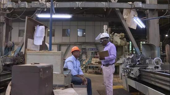 当地员工辛普森和技术总监詹姆斯在交流工作。新华社记者 朱晓光 摄