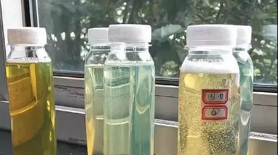 """▲山东临淄纪诺工贸公司,窗台上摆着多种成品油样品。其最左侧深黄色的所谓""""国三""""柴油,经检测硫含量超标300 多倍。新京报记者 大路 摄"""