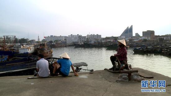 9月18日傍晚,在广西北海市侨港镇电建渔港,渔工正在等待捕捞船靠岸。