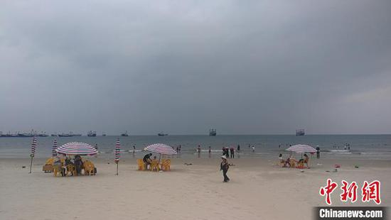 少量游客在侨港海滩上游玩。 翟李强 摄