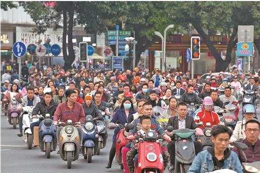 (2019年4月,晚高峰时段,众多市民骑电动自行车通过南宁市朝阳七岔路口,只有少部分市民佩戴头盔。 南国早报记者 邹财麟摄)