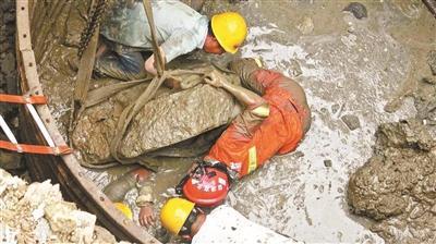 压在工人身上的水泥块被绑在挖掘机上吊出