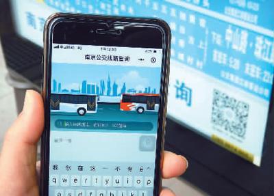 """南京新街口公交站站牌上新发布的""""南京公交线路查询""""微信小程序吸引着乘客。"""