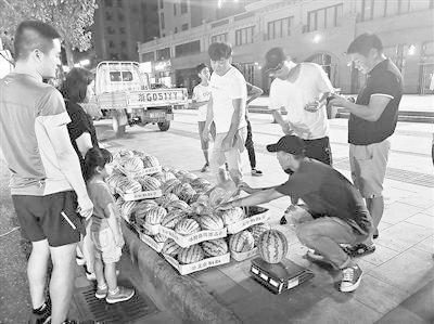 李恩慧(右一)每天晚上7点准时出摊卖西瓜