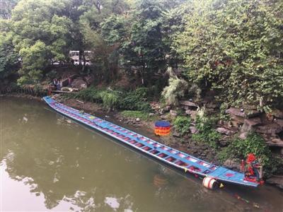 昨日,距翻船事故发生地百余米外,一艘龙舟停在桃花江边。