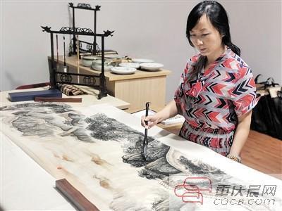 杨雪梅对带去北京的画进行最后润笔。