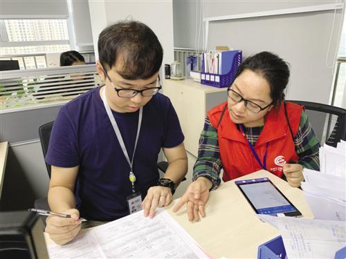 普查员张莉(右)一边指导公司财务人员填写经济普查表格,一边将数据同步录入PAD设备  记者 陈蕾摄