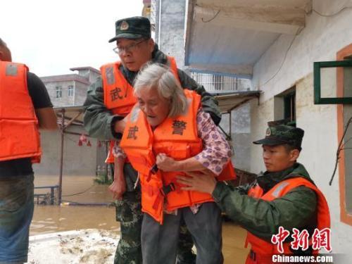 图为武警官兵转移受灾民众。 杨陈 摄