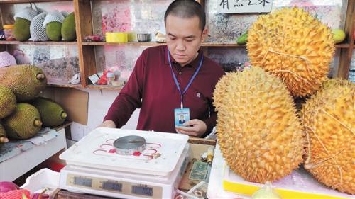 执法人员使用标准砝码检查水果店电子秤 本报见习记者 周粹莹 摄
