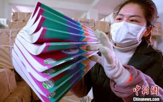 资料图:江西省吉安市泰和县新华书店工作人员在分拣清点新教材。 司马天民 摄