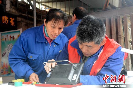 """刘汉平的""""雷锋街市""""为市民免费修理电器。 孙赟飞 摄"""