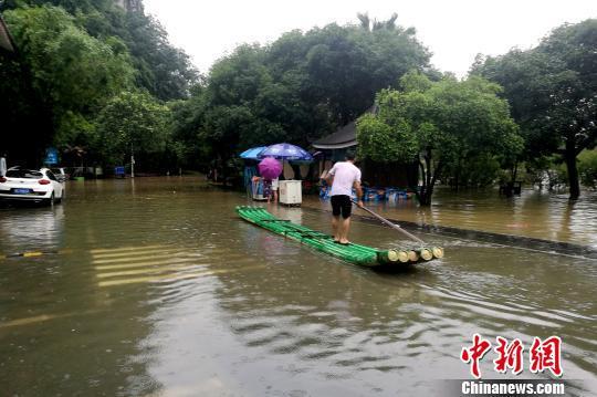 图为桂林穿山公园部分被淹,附近民众用竹笺出行。 唐梦宪 摄