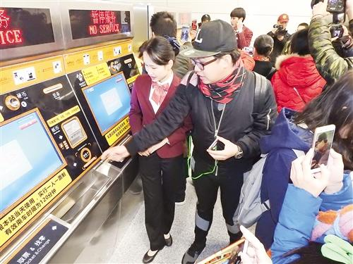 地铁工作人员向市民介绍无人购票机的使用方法记者赖有光摄