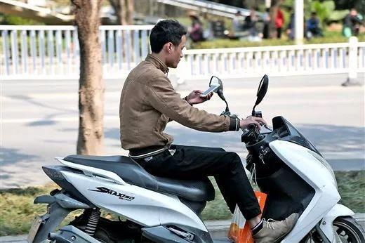 一名市民一边骑车一边看手机↑↑