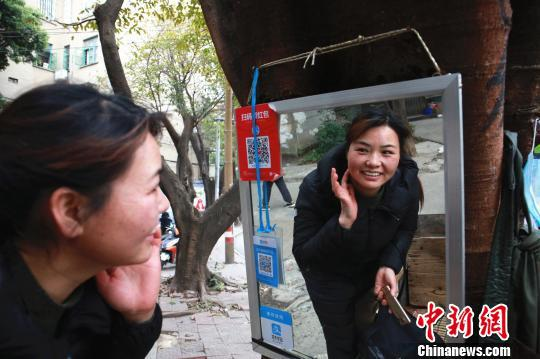 一名顾客绞脸后,用手摸着光滑的脸照镜子。 朱柳融 摄