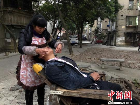 一名男子在体验绞脸。 朱柳融 摄