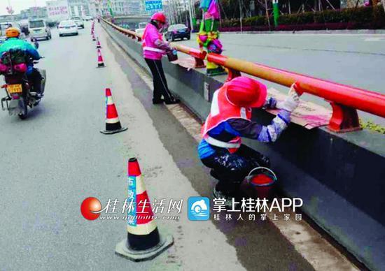 工人们正在北辰立交桥对防撞护栏进行涂装作业。  通讯员蒋炜 摄