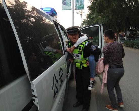 辅警黄志盛背着患病女生奔向警车