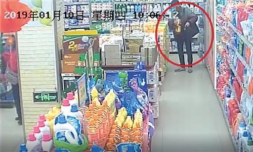 ◀班某在超市把花生油塞进公文包时被监控拍到 (视频截图)