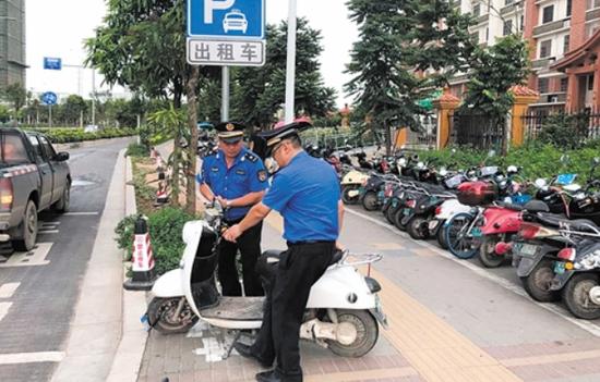 ▲城管队员在街头规范电动自行车停放秩序(高新区城管队供图)