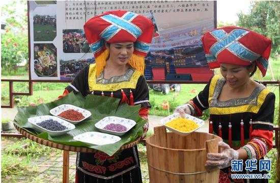 3月25日,在广西上林县巷贤镇,两名壮族女子在将浸泡好的五色糯米装入木桶里准备蒸制。新华社记者 陆波岸 摄