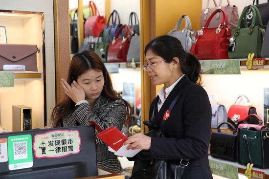 市分行员工向商铺里的店员介绍我行邮爱公益平台和邮爱自强班公益项目