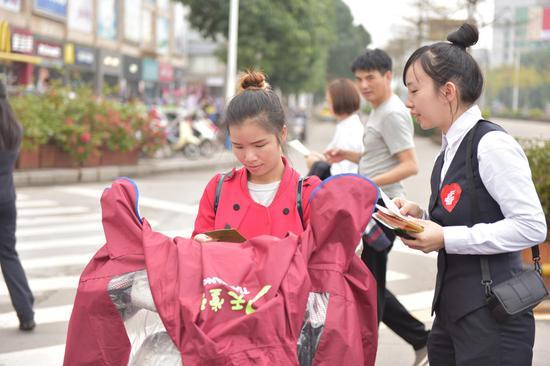 邮储银行钦州市分行员工向群众宣传邮爱公益活动