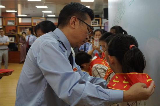 """南宁市国税局总经济师张仕龙为""""小小税法宣传员""""授予证书(李洁摄)"""