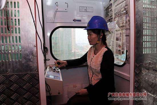 正在操作升降机的农民工  资料图片