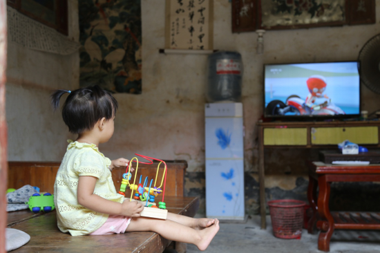 小钰在家族共用的客厅里看电视。 摄/黄媛