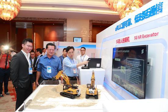 走进中国-东盟博览会:在第15届中国-东盟博览会上,嘉宾体验5G挖掘机远程操控应用