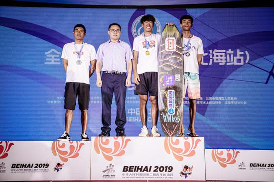 *北海市旅游文体局局长鲁性东为获得全国锦标赛双向板男子专业组前三名的运动员颁奖