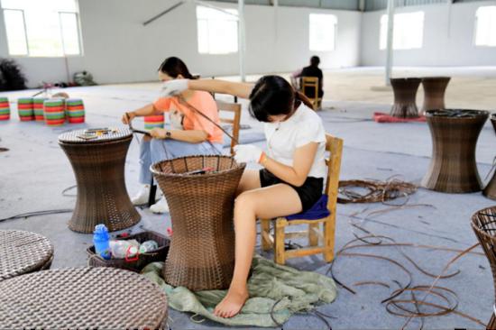 图为扶贫车间女工编织酒桶