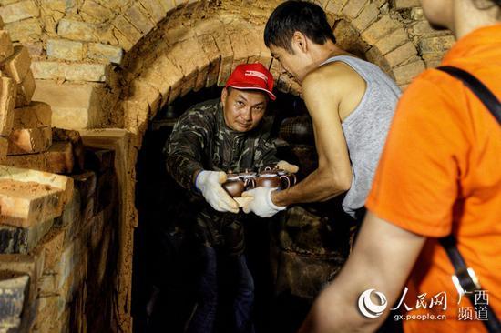 图为工作人员从钦江古龙窑内搬出坭兴陶。翟李强摄