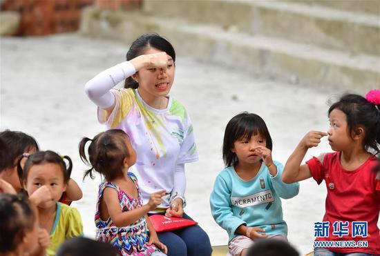 来自澳门的志愿者在给乌英苗寨的孩子们讲解卫生知识(8月10日摄)。
