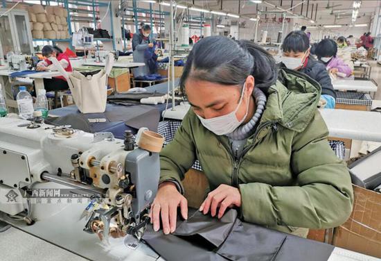 2月19日,在平乐县同安镇一家皮革生产企业扶贫车间,工人们经过体温检测、佩戴口罩等防护措施后投入到忙碌生产中。欧富强 摄
